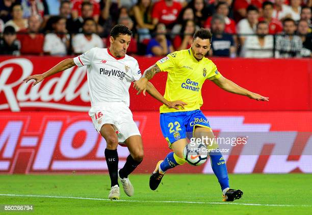 Sevilla's midfielder Jesus Navas vies with Las Palmas' defender Ximo Navarro Jimenez during the Spanish league football match Sevilla FC against UD...