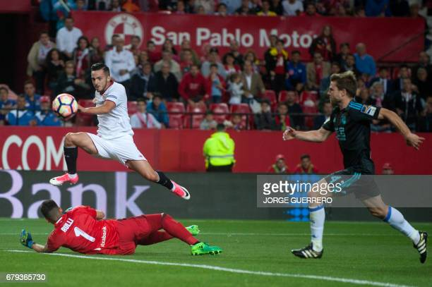 Sevilla's midfielder Pablo Sarabia scores past Real Sociedad's Argentinian goalkeeper Geronimo Rulli and midfielder Asier Illarramendi during the...
