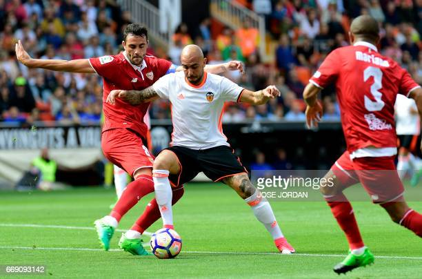 Sevilla's midfielder Vicente Iborra vies with Valencia's Italian forward Simone Zaza during the Spanish league football match Valencia FC vs Sevilla...
