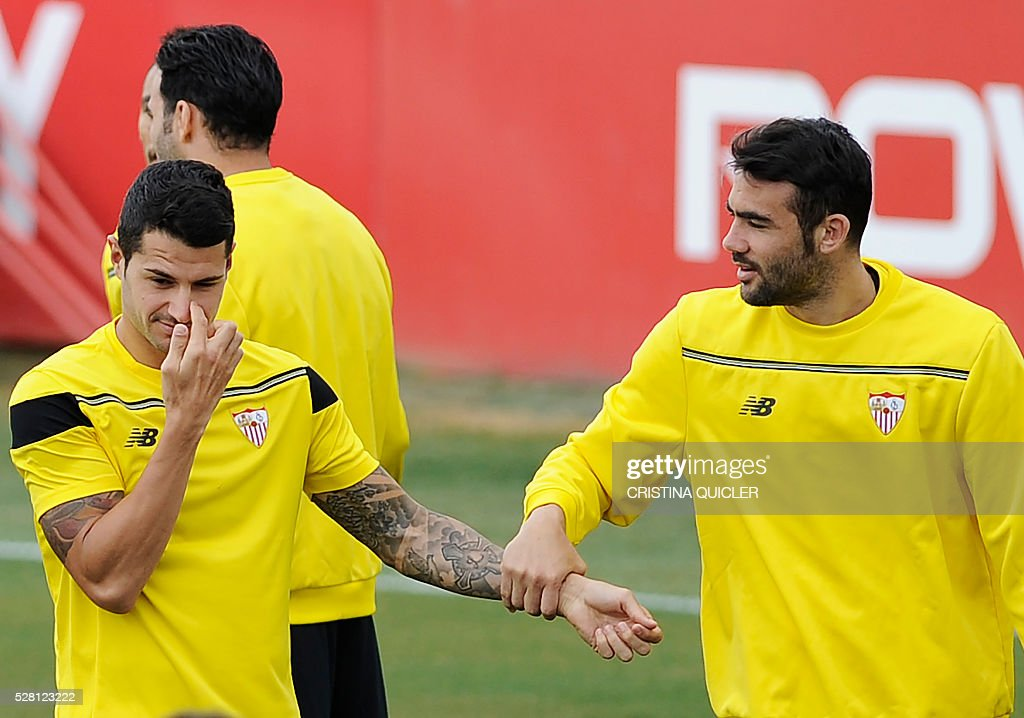 Sevilla's midfielder Vitolo (L) gestures past Sevilla's midfielder Vicente Iborra during a training session on May 4, 2016 on the eve of the UEFA Europa League semi-final second leg football match Sevilla FC vs Shakhtar Donetsk at the Ciudad Deportiva in Sevilla. / AFP / CRISTINA