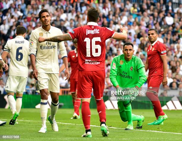 Sevilla's Montenegrin forward Stevan Jovetic protests to Real Madrid's French defender Raphael Varane beside Real Madrid's Costa Rican goalkeeper...