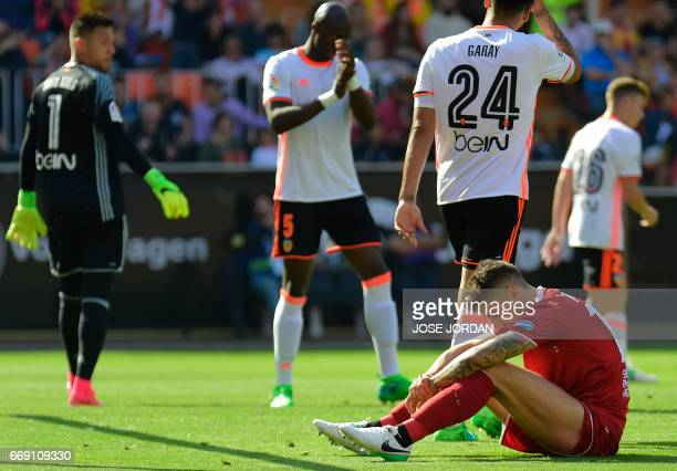 Sevilla's Montenegrin forward Stevan Jovetic sits on the field after missing an attempt on goal during the Spanish league football match Valencia CF...