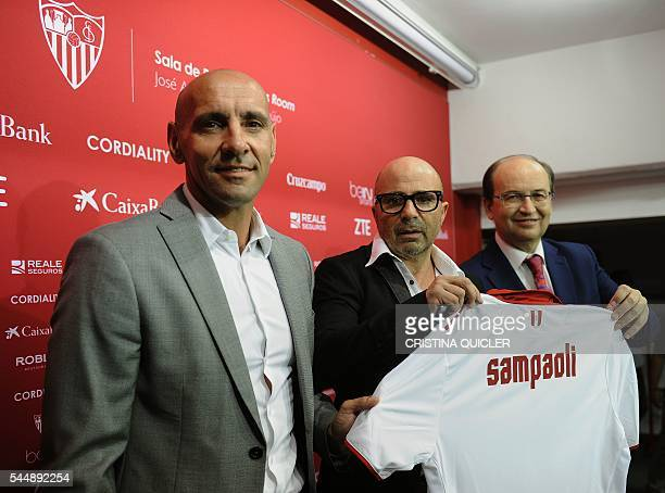 Sevilla's new Argentinian coach Jorge Sampaoli holds a jersey with his name between Sevilla's President Jose Castro and technical director Monchi...