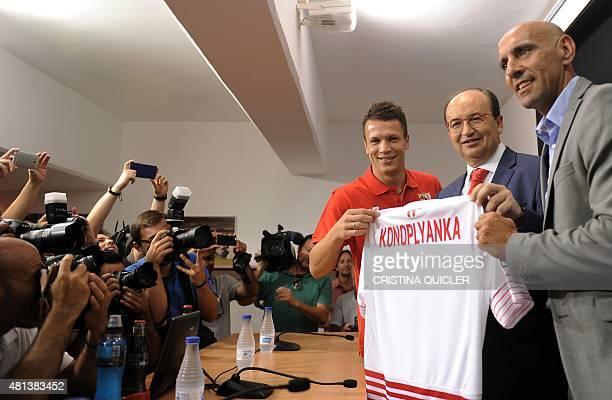 Sevilla's new player Ukrainian midfielder Yevhen Konoplyanka poses with Sevilla's president Jose Castro and Sevilla's director of football Monchi as...