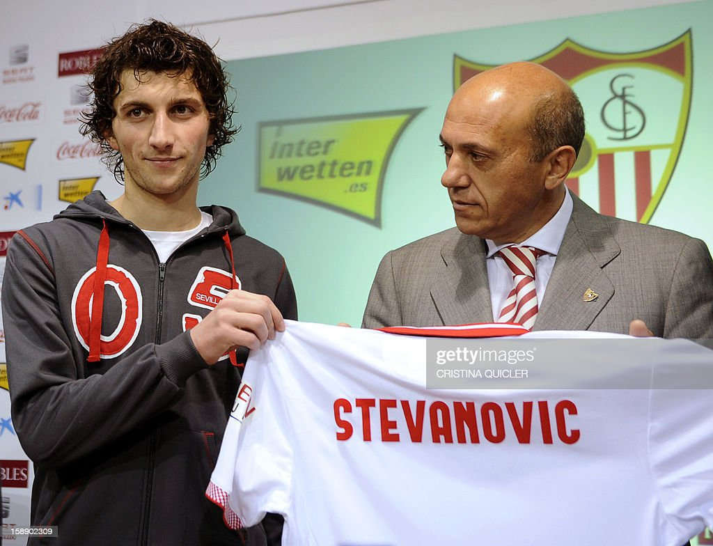 Sevilla's new signing, Bosnian midfielder Miroslav Stevanovic (L) holds a jersey with his name as he poses with Sevilla's president Jose Maria del Nido during his presentation to the media in Sevilla on January 3, 2013. Spanish league football club FC Sevilla signed Bosnian international midfielder Miroslav Stevanovic, 22, from Serbian club FK Vojvodina for around 1.6 million euros (2.11 million USD).
