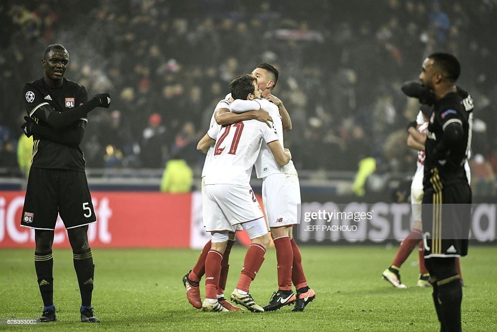 TOPSHOT - Sevilla's players celebrate (C) as Lyon's French forward Alexandre Lacazette (R) and Lyon's defender Mouctar Diakhaby (L) react at the end of the UEFA Champions League Group H football match between Olympique Lyonnais (OL) and FC Sevilla at the Parc Olympique Lyonnais in Décines-Charpieu near Lyon, southeastern France, on December 7, 2016. Last season's Europa League winners Sevilla drew 0-0 with Lyon to take the runners-up spot in Group H. / AFP / JEFF