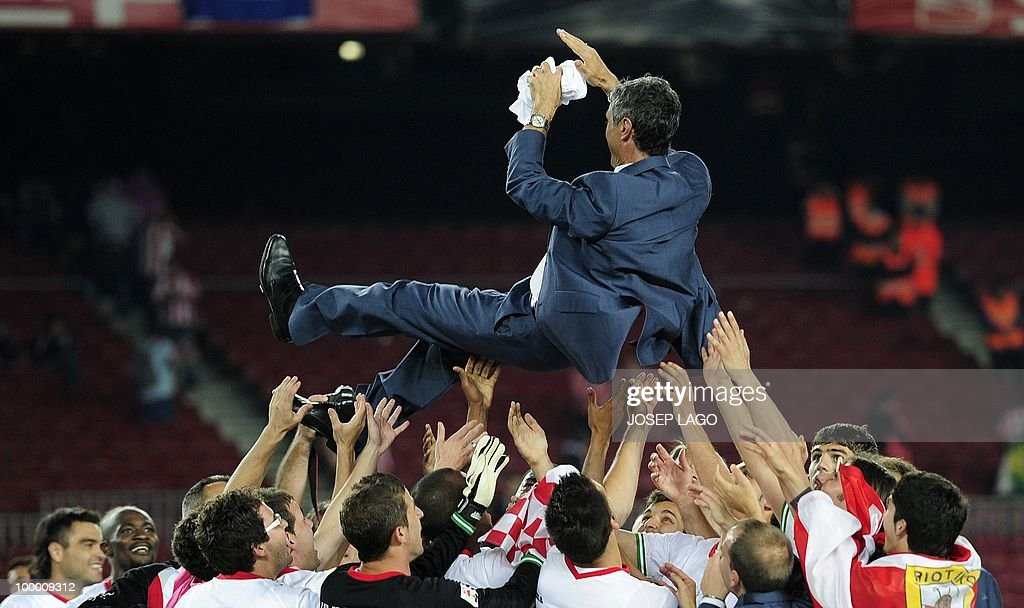 Sevilla's players celebrate with their coach Antonio Alvarez Giraldez after winning the King's Cup final match against Atletico Madrid at the Camp Nou stadium in Barcelona on May 19, 2010. Sevilla won 2-0.