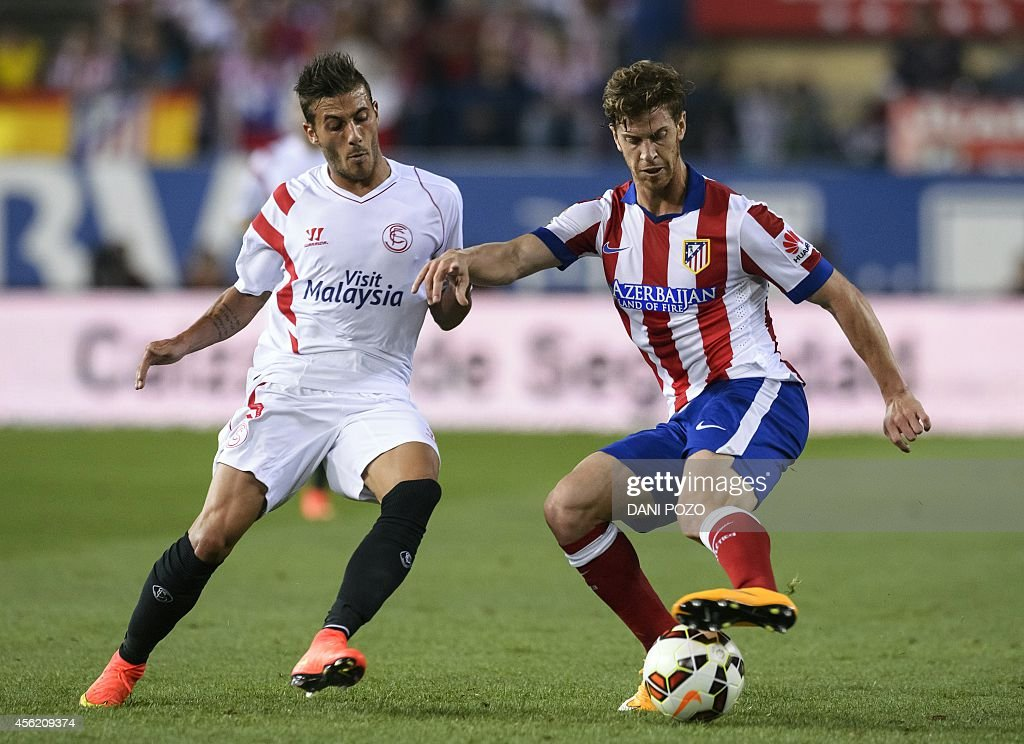 Sevilla's Portuguese defender <a gi-track='captionPersonalityLinkClicked' href=/galleries/search?phrase=Diogo+Figueiras&family=editorial&specificpeople=10127097 ng-click='$event.stopPropagation()'>Diogo Figueiras</a> (L) vies with Atletico Madrid's Argentinian defender Cristian Ansaldi during the Spanish league football match Club Atletico de Madrid vs Sevilla FC at the Vicente Calderon stadium in Madrid on September 27, 2014. AFP PHOTO / DANI POZO