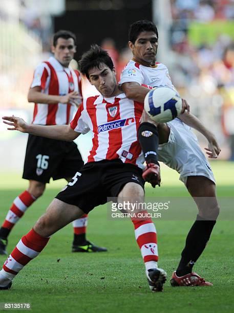 Sevilla's Renato vies with Athletic de Bilbao's Amorebieta during a Spanish league football match at the Sanchez Pizjuan stadium in Sevilla on...