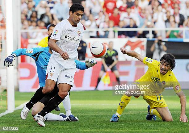 Sevilla's Renato vies with Villarreal's Javi Venta and goalkeeper Diego Lopez during a Spanish football match at the Sanchez Pizjuan stadium in...