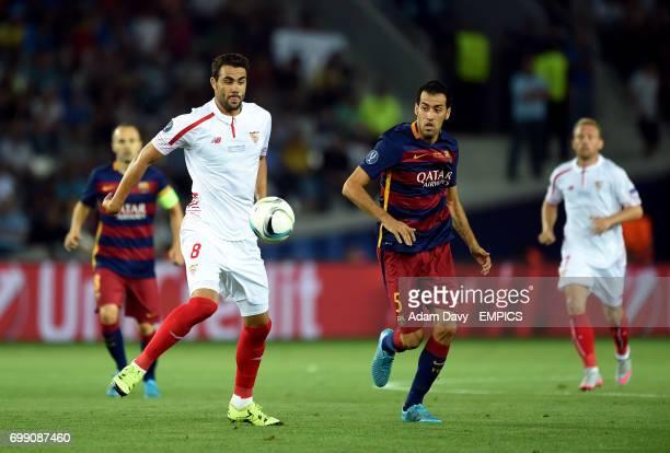 Sevilla's Vicente Iborra and Barcelona's Sergio Busquets battle for the ball