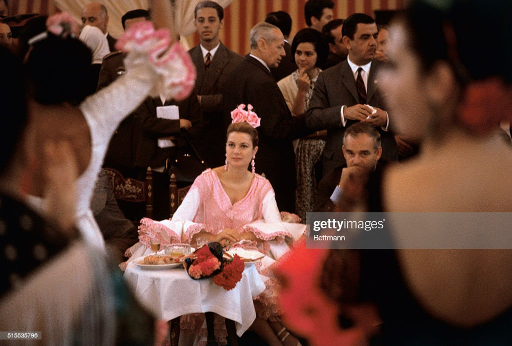 American-born Princess Grace of Monaco and her husband, Prince Rainier, attend a Flamenco Fiesta. Princess Grace, wearing a traditional frilly Andalusian dress, and her husband were joined by Mrs. John F. Kennedy and her party.