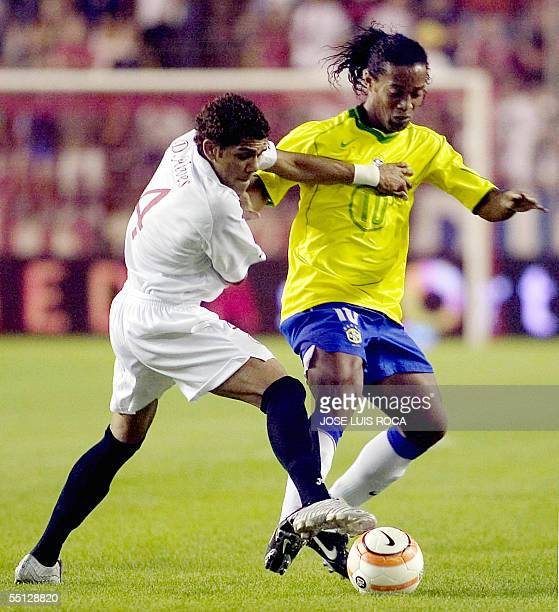 Ronaldinho of Brazil vies with Seville's player Daniel Alves during their friendly football match SevilleBrazil at the Sanchez Pizjuan stadium in...
