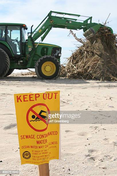 A sewage contaminated water sign in front of a tractor cleaning up debris on Huntington State Beach