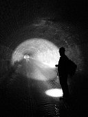 Sewage inspector shining torch in tunnel