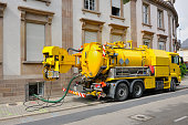 Sewage - sewerage - truck on city street in working process to clean up sewerage overflows, cleaning pipelines and potential pollution issues from an modern building. This type of truck is used for re