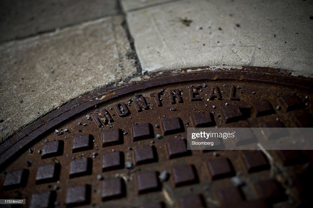 A sewer grate sits on a sidewalk in Montreal, Quebec, Canada, on Monday, July 8, 2013. Montreals city council elected Laurent Blanchard as interim mayor to replace Michael Applebaum, who quit last week after being arrested on corruption charges. Photographer: Brent Lewin/Bloomberg via Getty Images