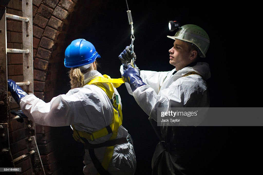 Sewer worker Harry Calder (R) helps lower a visitor into the Northern Outfall Sewer at Wick Lane depot on May 25, 2016 in London, England. The sewer was designed by British engineer Joseph Bazalgette following the 'Great Stink' of 1858 and is today worked on by sewer technicians known as 'Flushers'. Thames Water marks Sewage Week this week with a series of events inviting members of the public down into the underground sewer network and around the Abbey Mills pumping station in east London.
