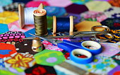 Cotton reels,thimble and scissors on a homemade patchwork quilt