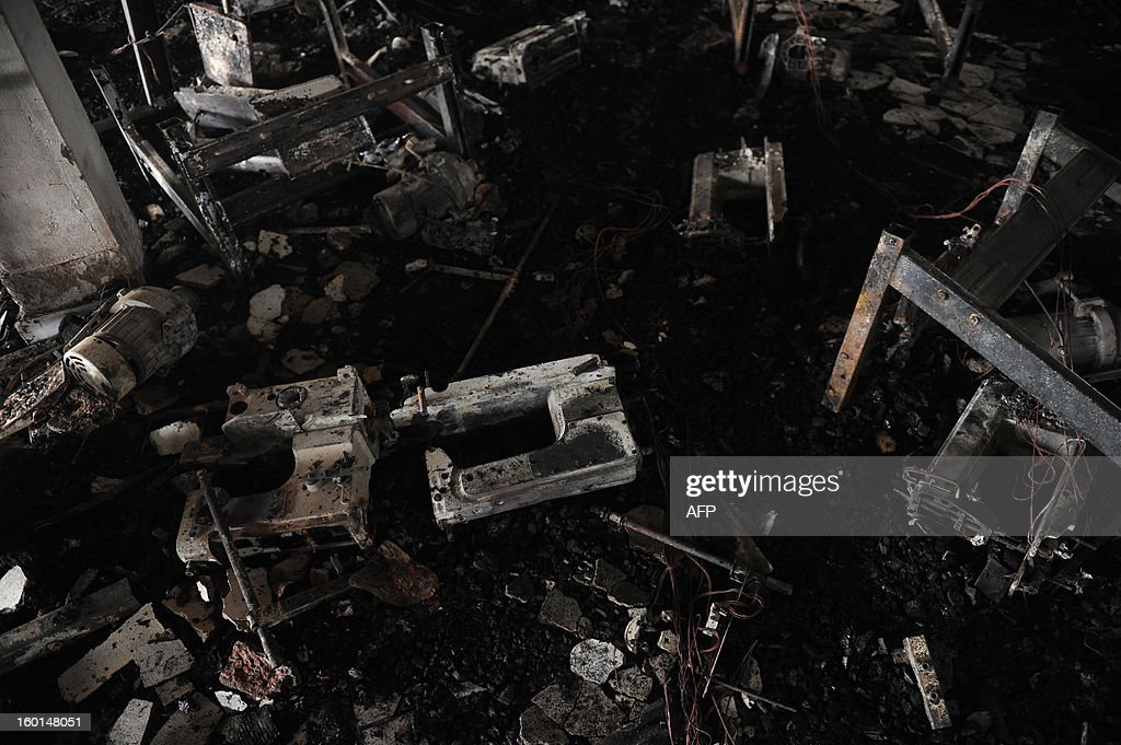 Sewing machines lie amongst devastation after a fire swept though the garment factory in Dhaka on January 27, 2013. At least seven female workers were killed on January 26 after a blaze swept through a small garment factory in the Bangladeshi capital of Dhaka, police and fire officials said. AFP PHOTO / Munir uz ZAMAN