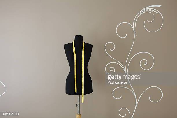 Sewing mannequin against a decorated wall