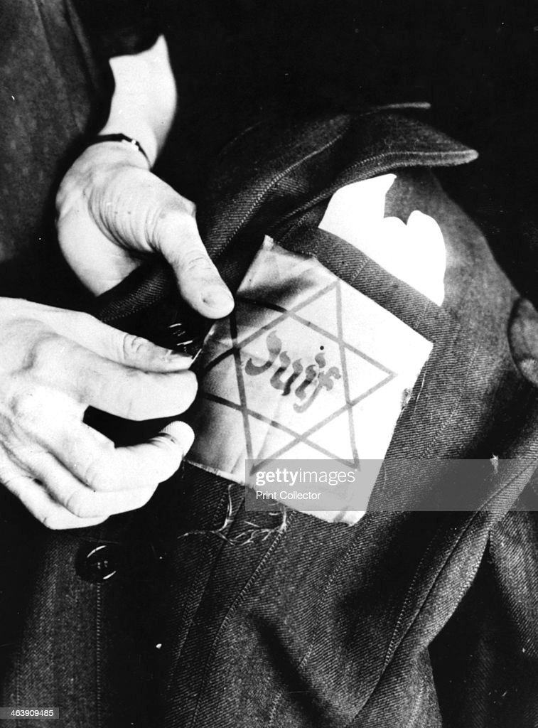 Sewing the yellow star identifying a Jew onto a jacket Germanoccupied Paris 1942 Life for French Jews became increasingly oppressive under Nazi...