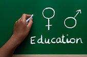 African American educator writing sex education on green chalkboard