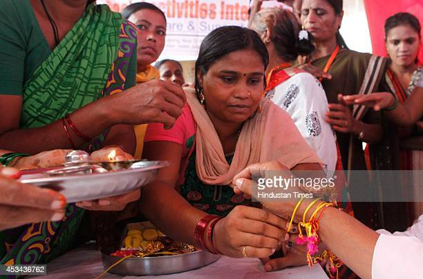 Sex workers tie the Rakhis to the NGO activists during an event held on the occasion of Raksha Bandhan organized by the NGO Social Activities...