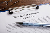 Close-up Of Sexual Harassment Complaint Form With Pen At Desk