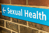 Blue sign on a brick wall, with the text 'Sexual Health'.