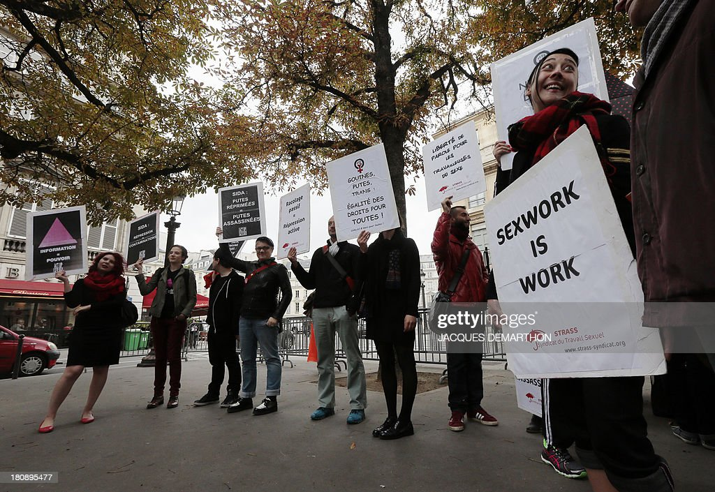 Sexual work union (STRAS) members gather holding placards to protest against a plan to penalized the clients of prostitution, on September 17, 2013 in Paris. AFP PHOTO/ JACQUES DEMARTHON