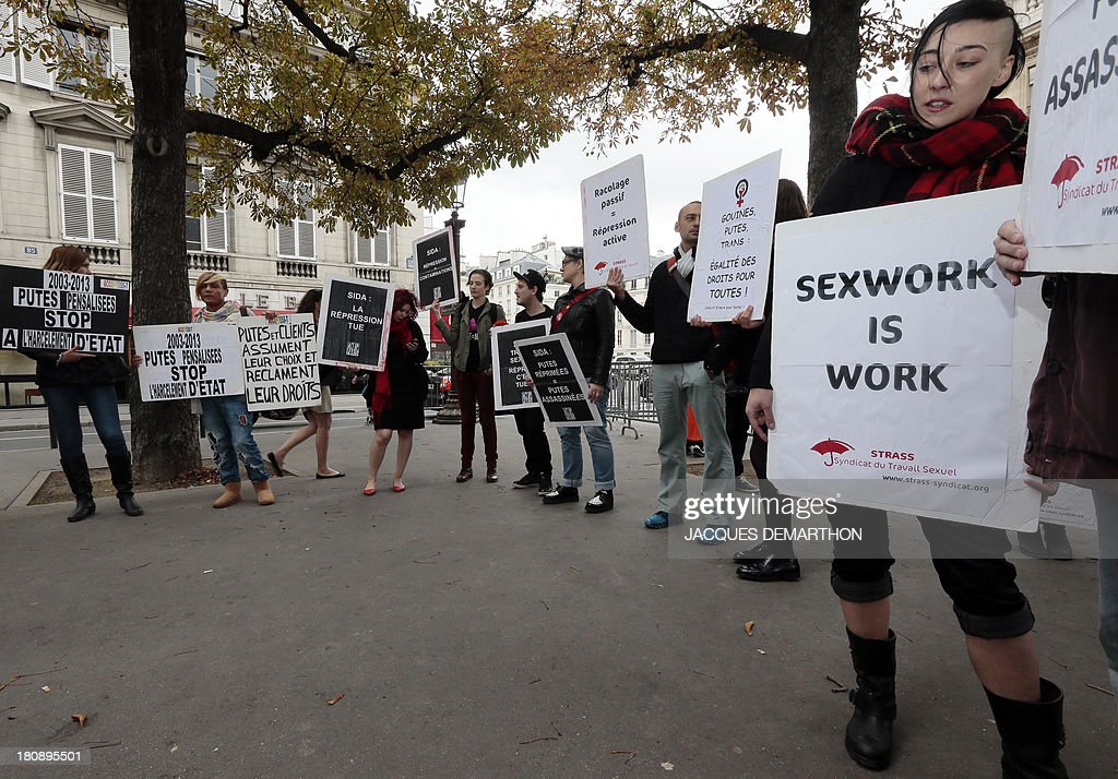 Sexual work union (STRAS) members gather holding placards to protest against a plan to penalized the clients of prostitution, on September 17, 2013 in Paris.