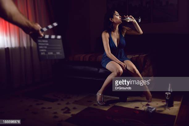 Sexy actress drinking champagne in bedroom
