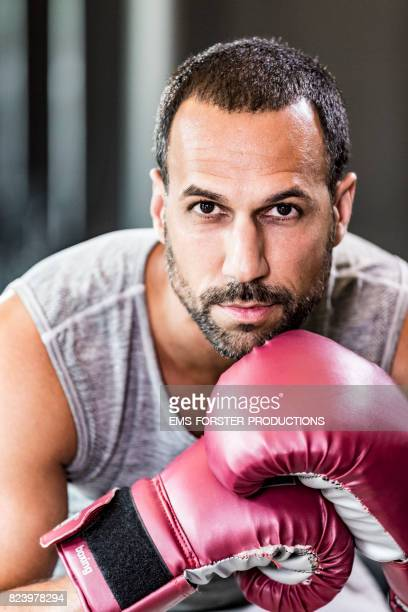 sexy and flirty fitness trainer wearing boxing gloves  while starring into the camera
