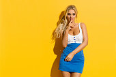 Cheerful sexy blond woman in blue white mini dress is holding finger on lips and looking at camera. Three quarter length studio shot on yellow background.