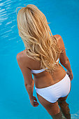 Rear view of a beautiful and sexy young blond woman wearing a white bikini walking into a turquoise blue swimming pool. Spa, healthy living and health club concept.