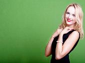 Sexy blonde businesswoman on green background