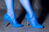 Female legs are in blue socks and sexy blue high heels shoes on gray background.