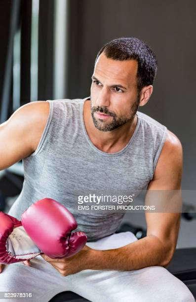 sexy fitness man is sitting in on a sport bench while holding some boxing gloves