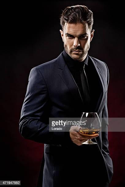 セクシーな男性のウィスキーを持つガラス