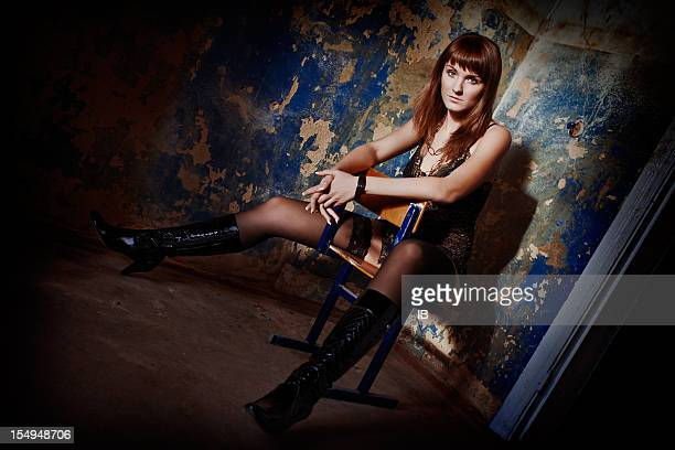 Sexy girl is sitting on a chair in old room