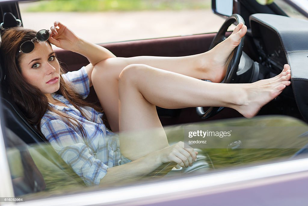 Sexy girl put her feet on wheel in the car : Foto de stock
