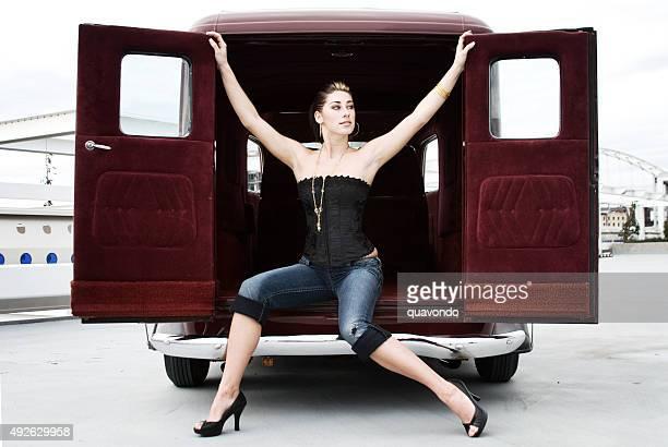 Sexy hotrod babe sitting on car.