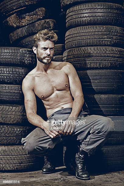 sexy male mechanic sitting in front of tires