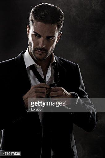 sexy man fixing his tie