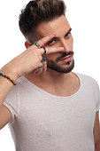 sexy man holding 2 fingers on his eye , making peace sign on white background
