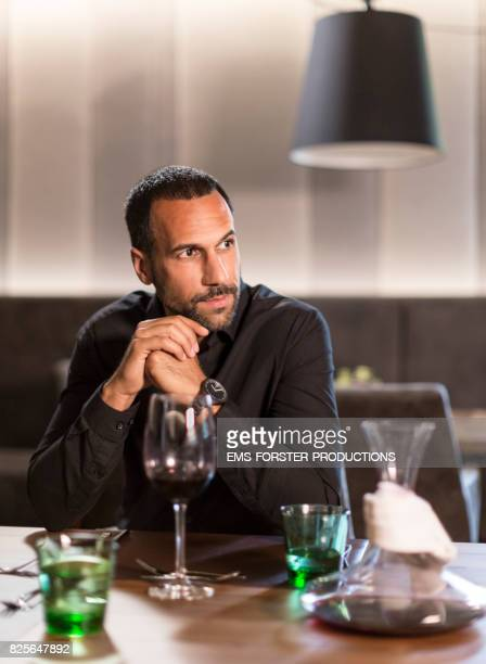 sexy man is waiting for his wife in a modern hotel restaurant