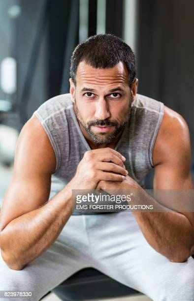 sexy man with three day beard an furrows is starring into the camera while sitting in a gym