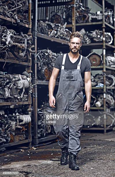 sexy mechanic walking in front of car engines