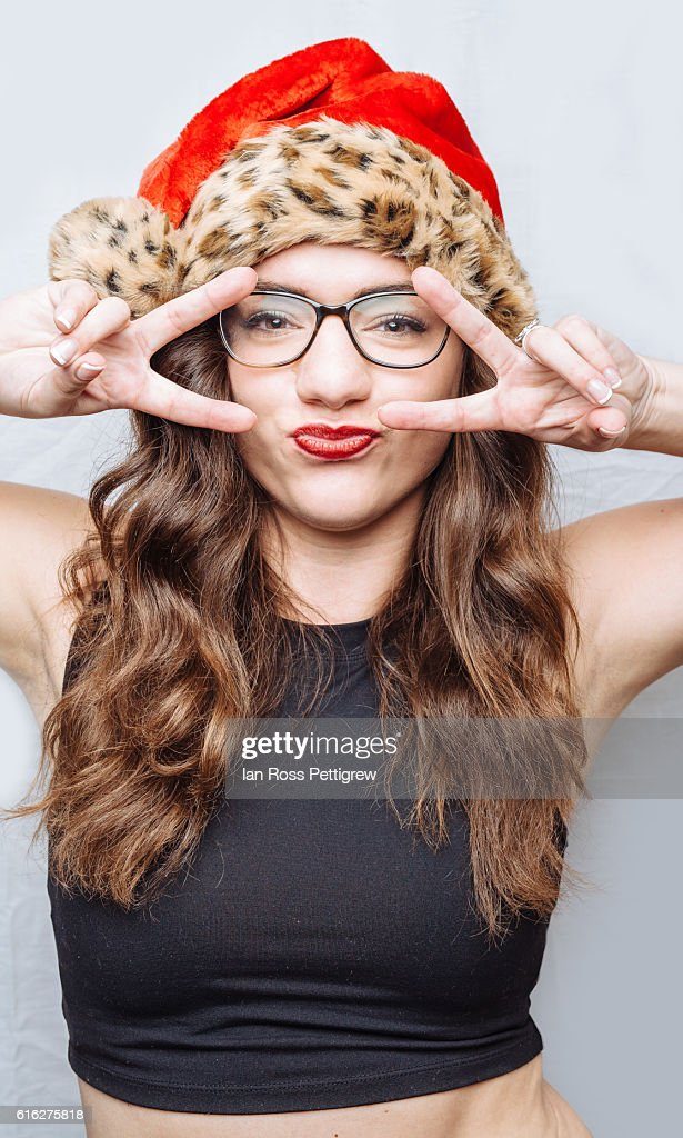 Sexy model wearing a Santa hat, hands up to face : Stock Photo